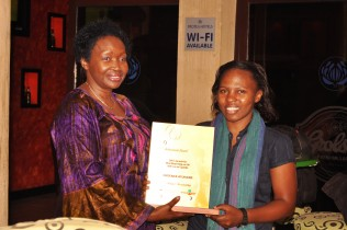 Minister of Finance, Hon. Maria Kiwanuka, presents Patience Atuhaire with a prize for her broadcast report.