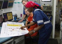 Joan Namukasa, a Tullow Uganda drilling engineer, reviews technical reports with colleagues at a rig site (Photo: Tullow Oil Uganda)