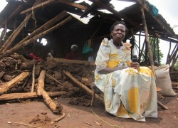 Beatrice Ngonzebwa sits outside her demolished home (Photo: S.Mwesigye)