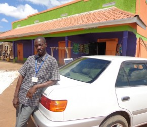 Gilbert Manyireki leans on his new car. In the background is his commercial building in Nzorobi village. (Photo: F. Mugerwa)