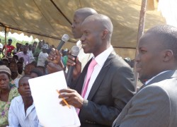 An official from the Chief Government Valuer (Center) speaks to residents in Buseruka as SFI's Director of Programs, Kosea Wamboka (Right) looks on. (Photo: F. Mugerwa)