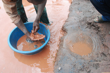 A miner in Mubende 'washing' crushed, fine iron ore with mercury. Photo by Beatrice Ongede